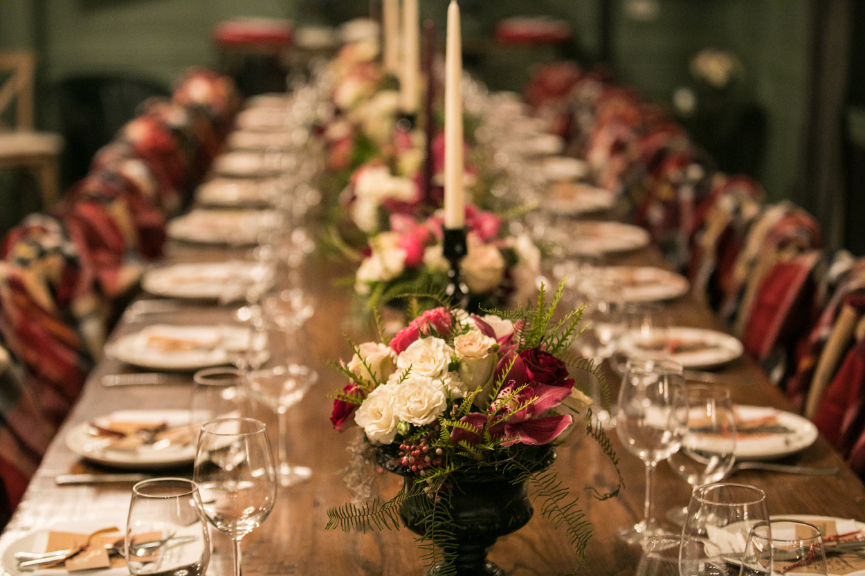 tapered candles at long table for holiday party, how to throw a holiday party
