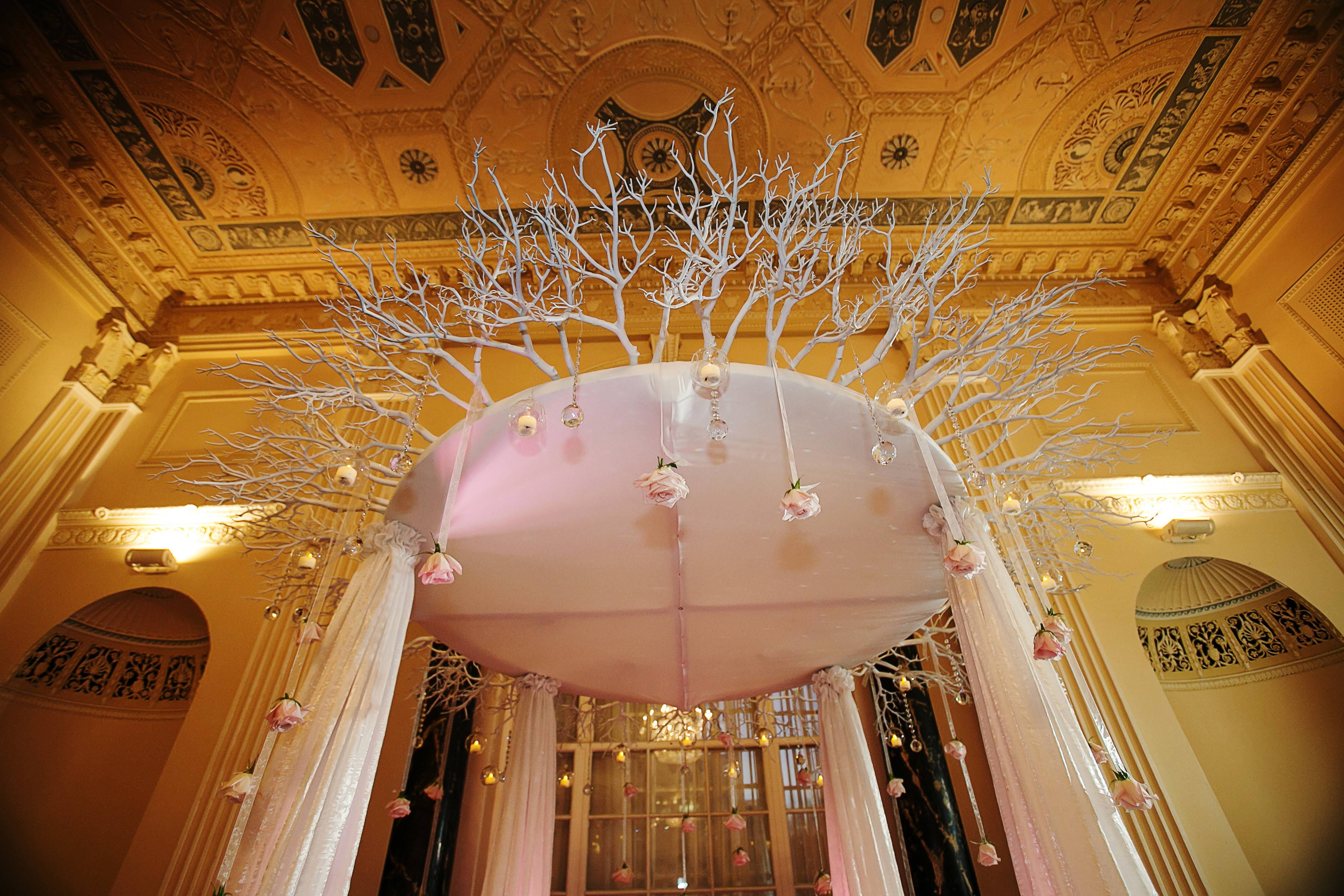 all-white winter ceremony arbor with christmas ornaments