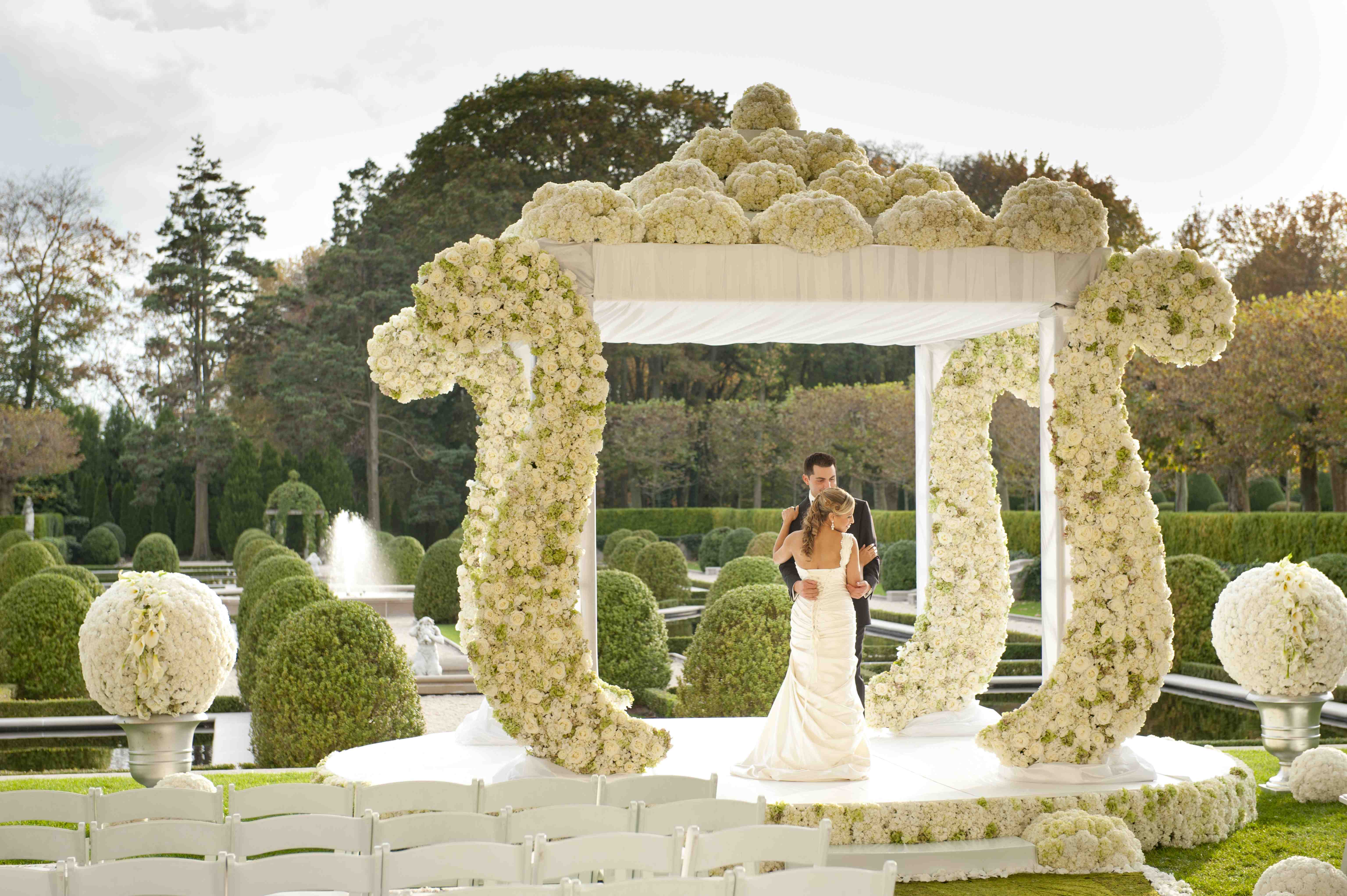 large wedding arbor with white flowers and whimsical design