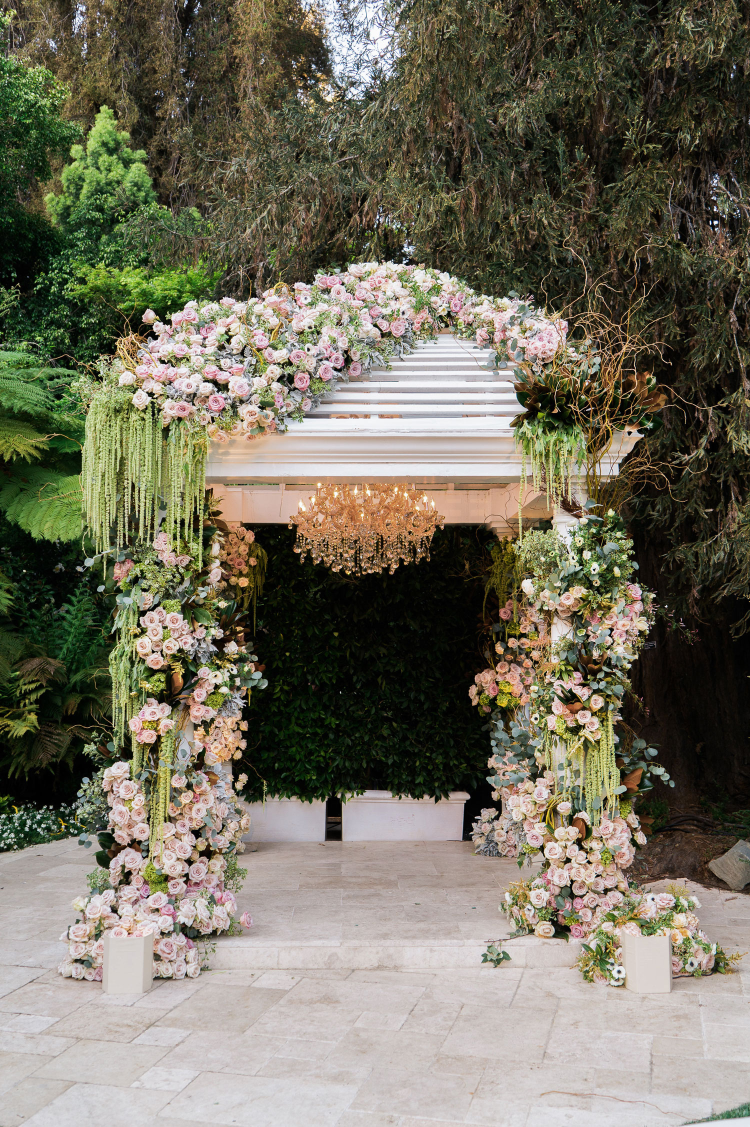 lush wedding ceremony arbor with amaranthus, pink flowers, and golden chandelier