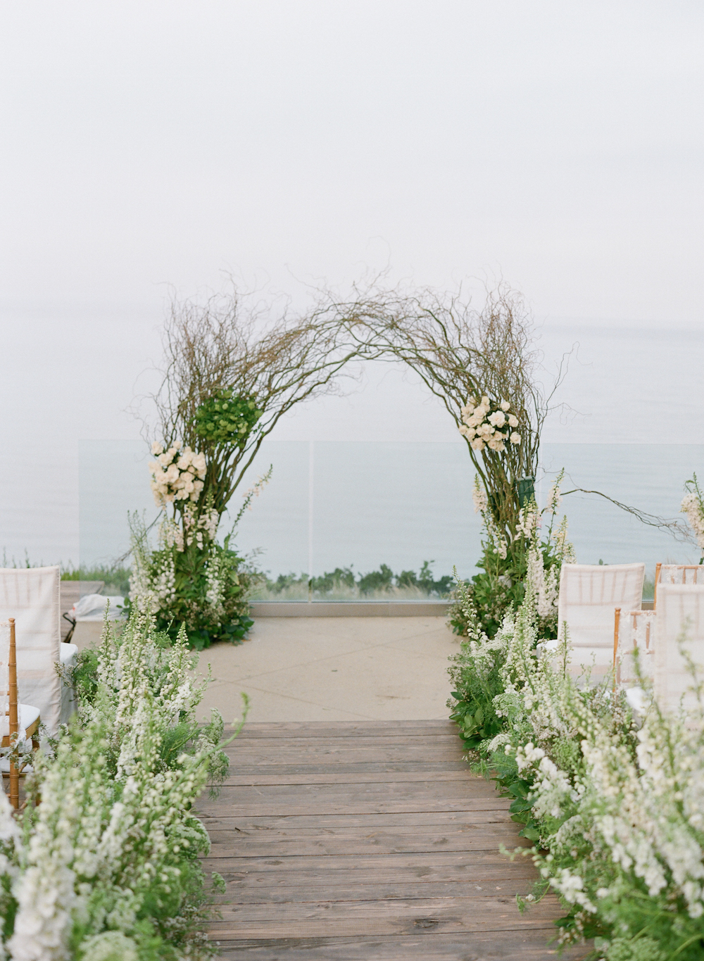 ocean view wedding ceremony with arch made from branches