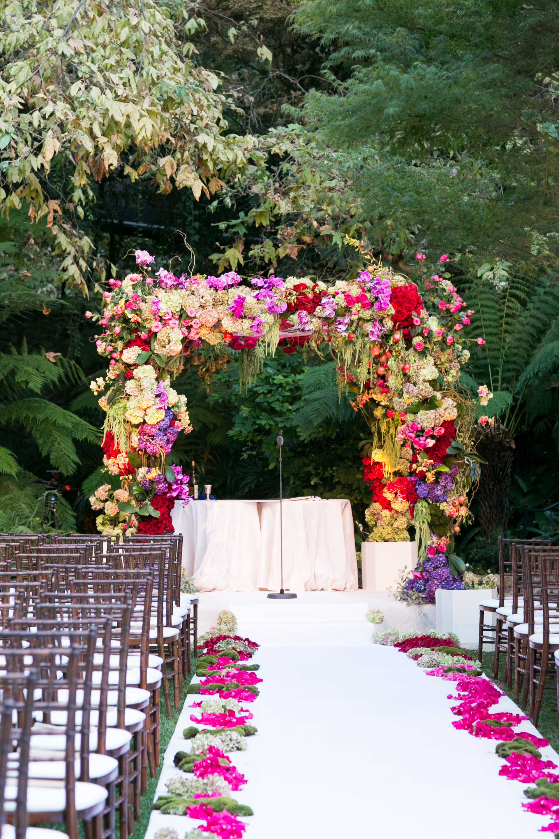 colorful chuppah with bright pink flowers and greenery