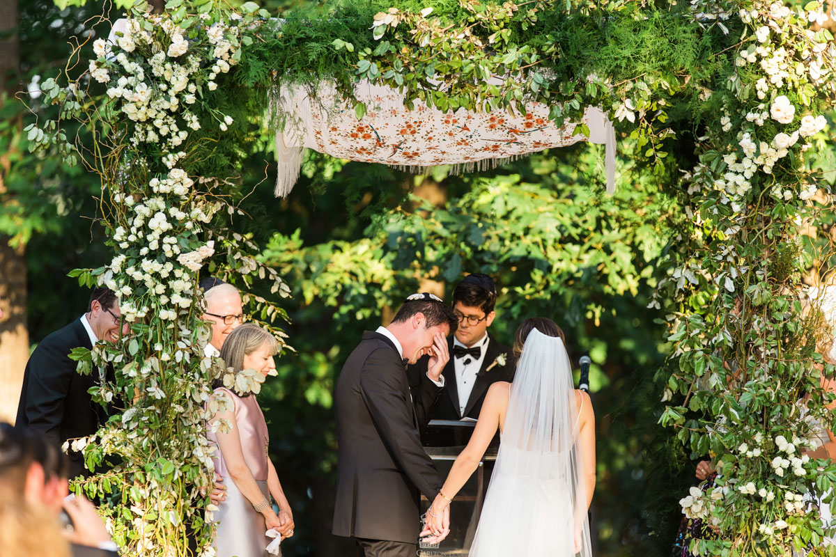 outdoor jewish wedding chuppah with lots of greenery and white flowers, floral tallit