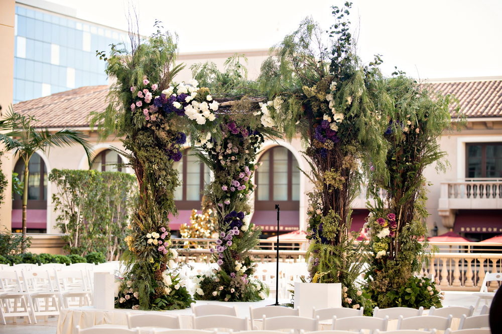rustic outdoor chuppah with purple flowers, greenery, and branches