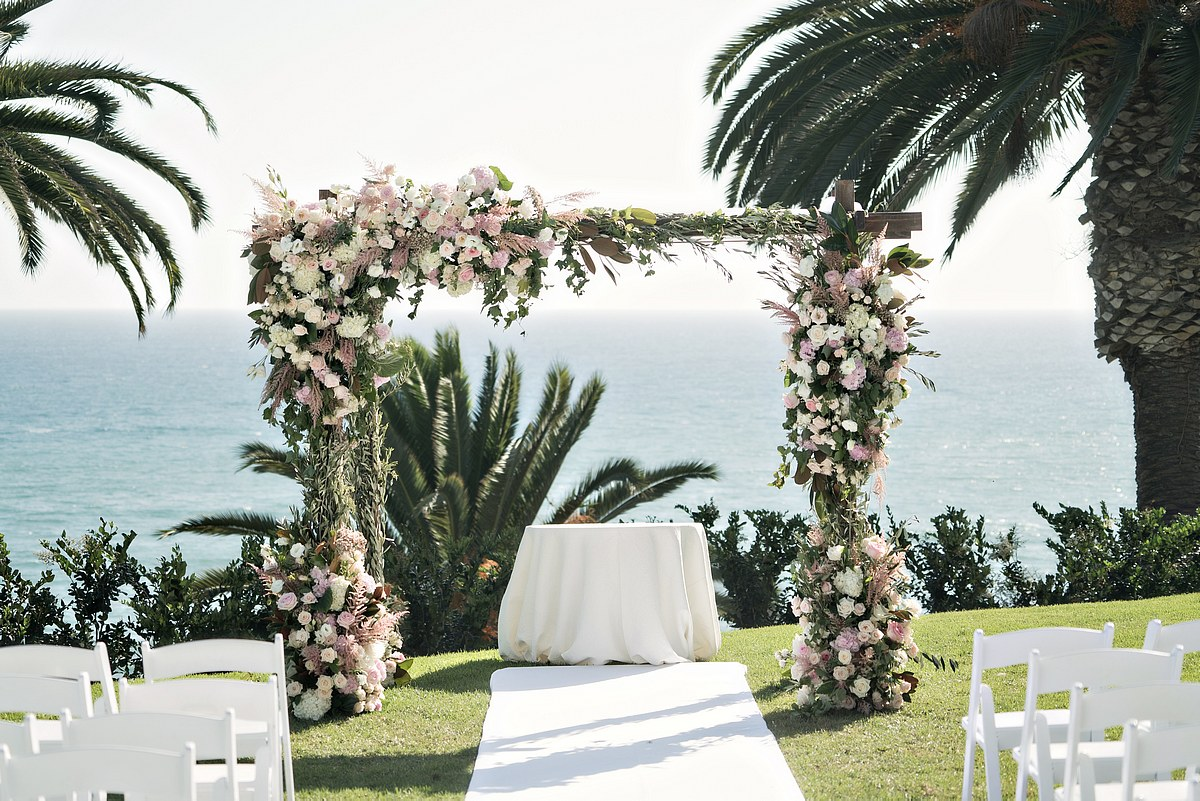 wooden chuppah with blush and ivory flowers, greenery, ocean views