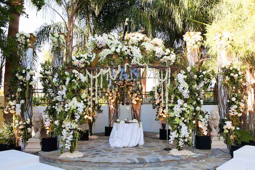 domed chuppah with garland of flowers and couple's first initials