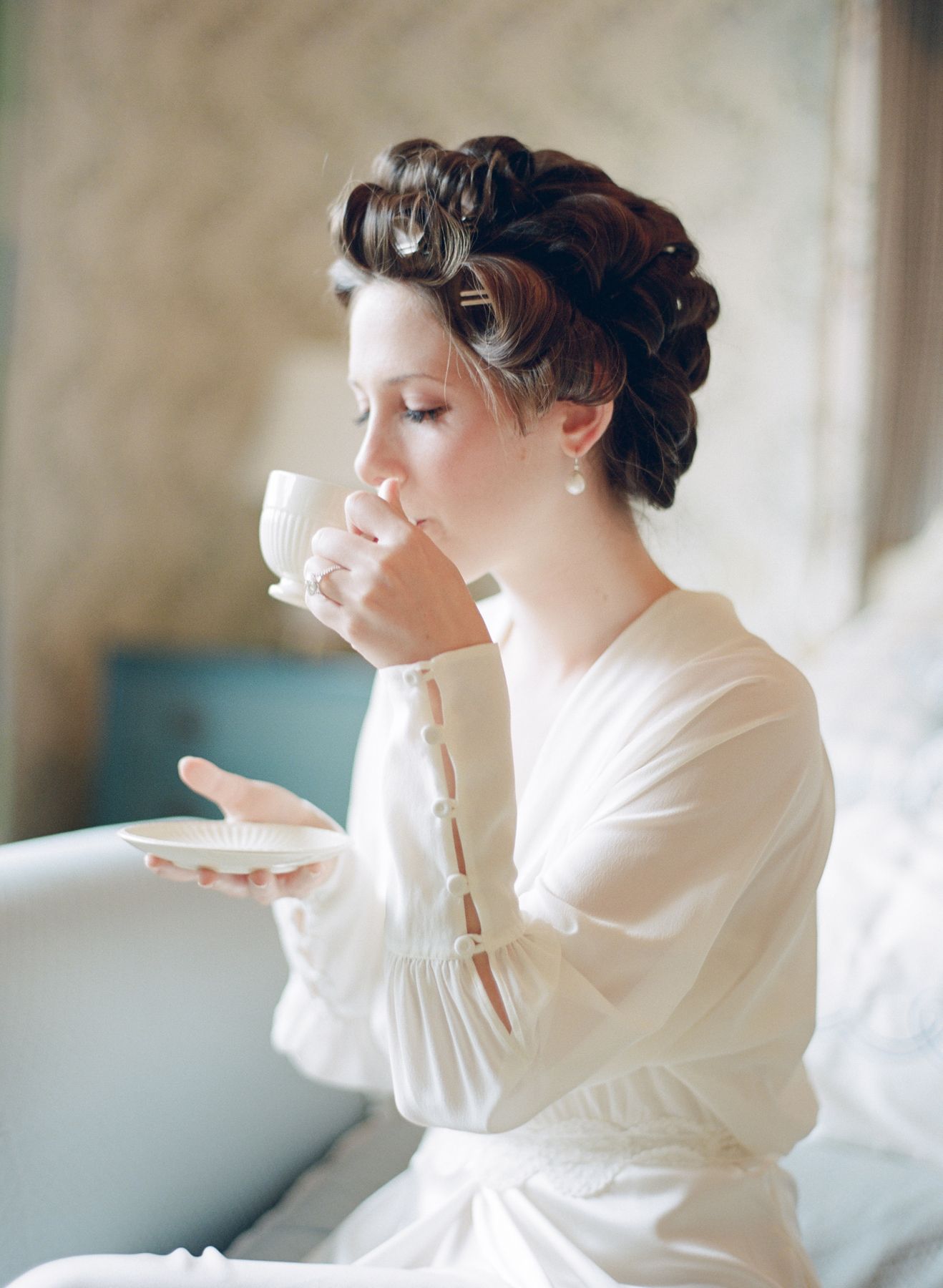 Bride in hair curlers sipping tea and getting ready for wedding