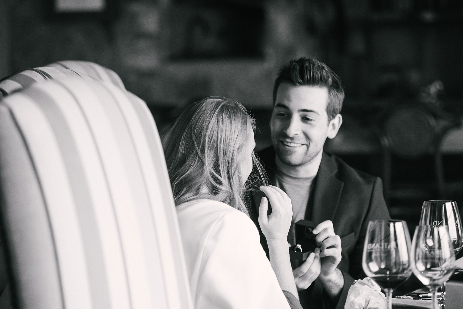 Black and white photo of groom surprising bride with engagement ring while wine tasting