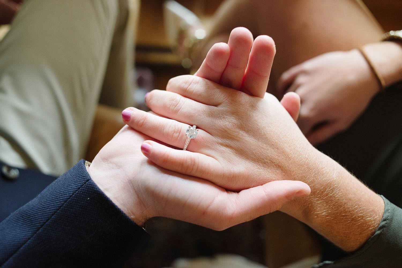 Close up of diamond engagement ring and diamond band setting proposal