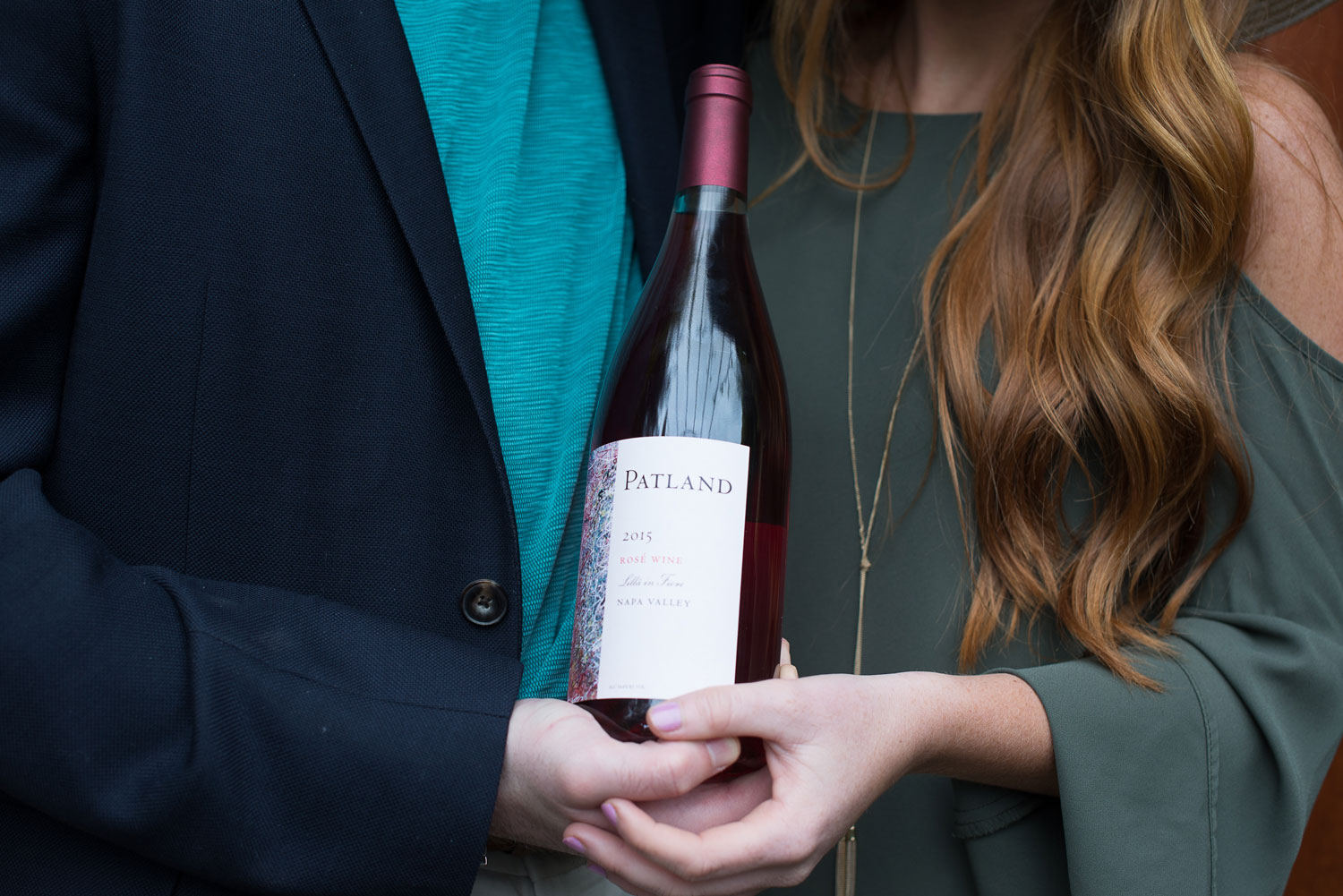 Bride and groom with bottle of wine from winery where groom proposed