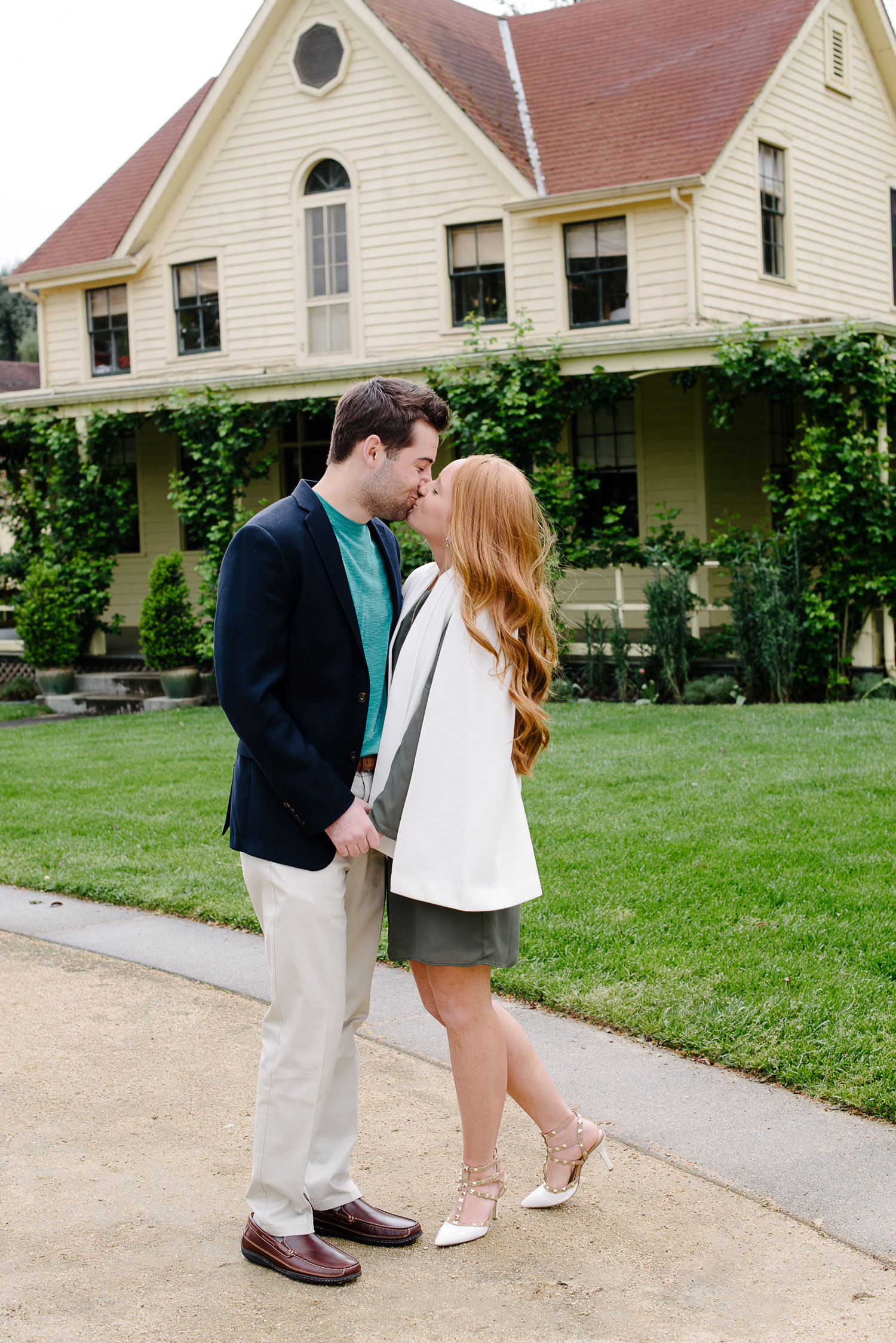 Bride in green dress and white cape jacket kissing groom after proposal wine country