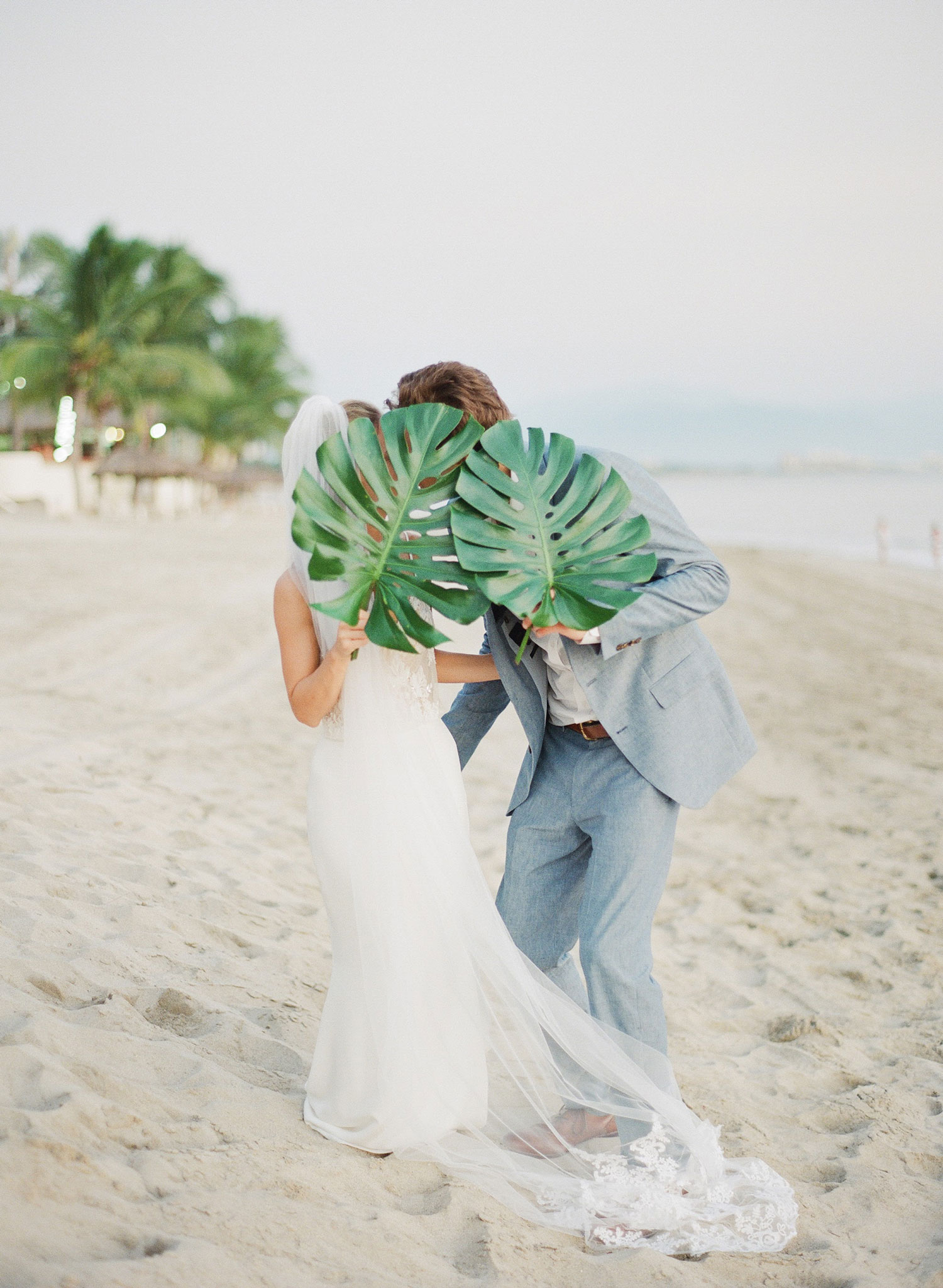 Bride and groom on sand destination wedding with tropical palm frond leaves in face