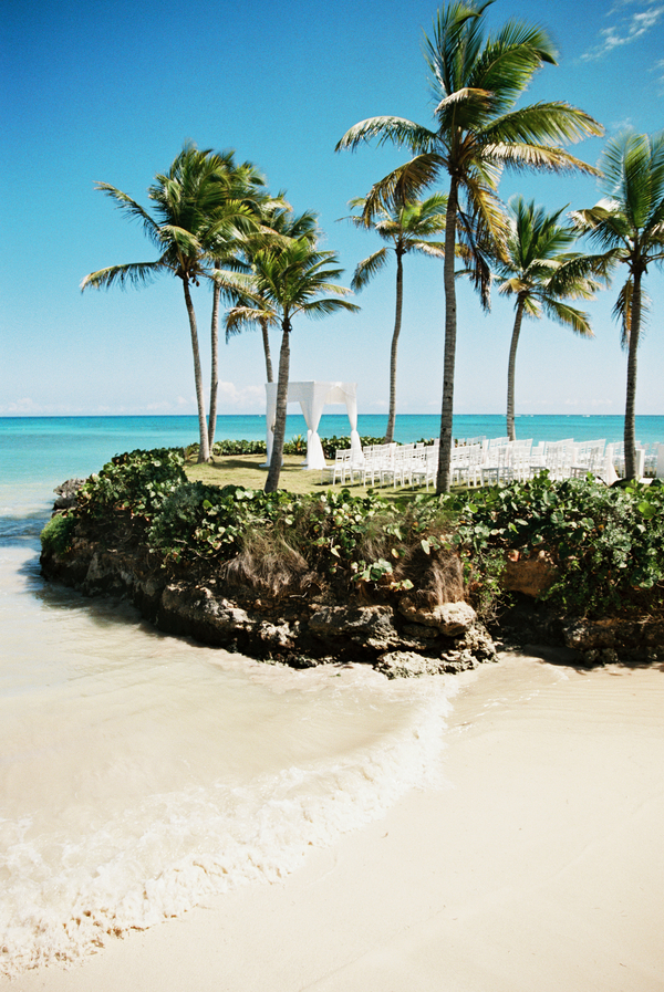 Destination wedding ceremony on bluff overlooking ocean by beach