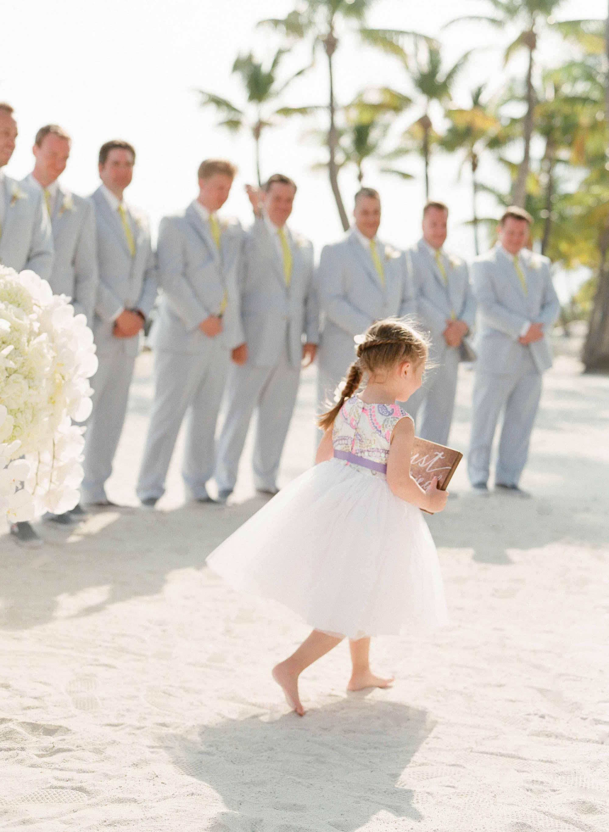 Flower girl walking in sand destination wedding ceremony on beach