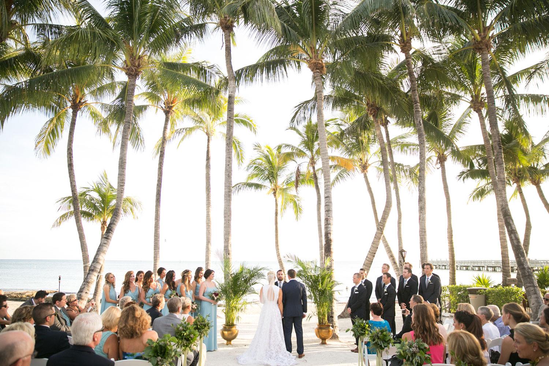 Destination wedding ceremony on beach under palm trees