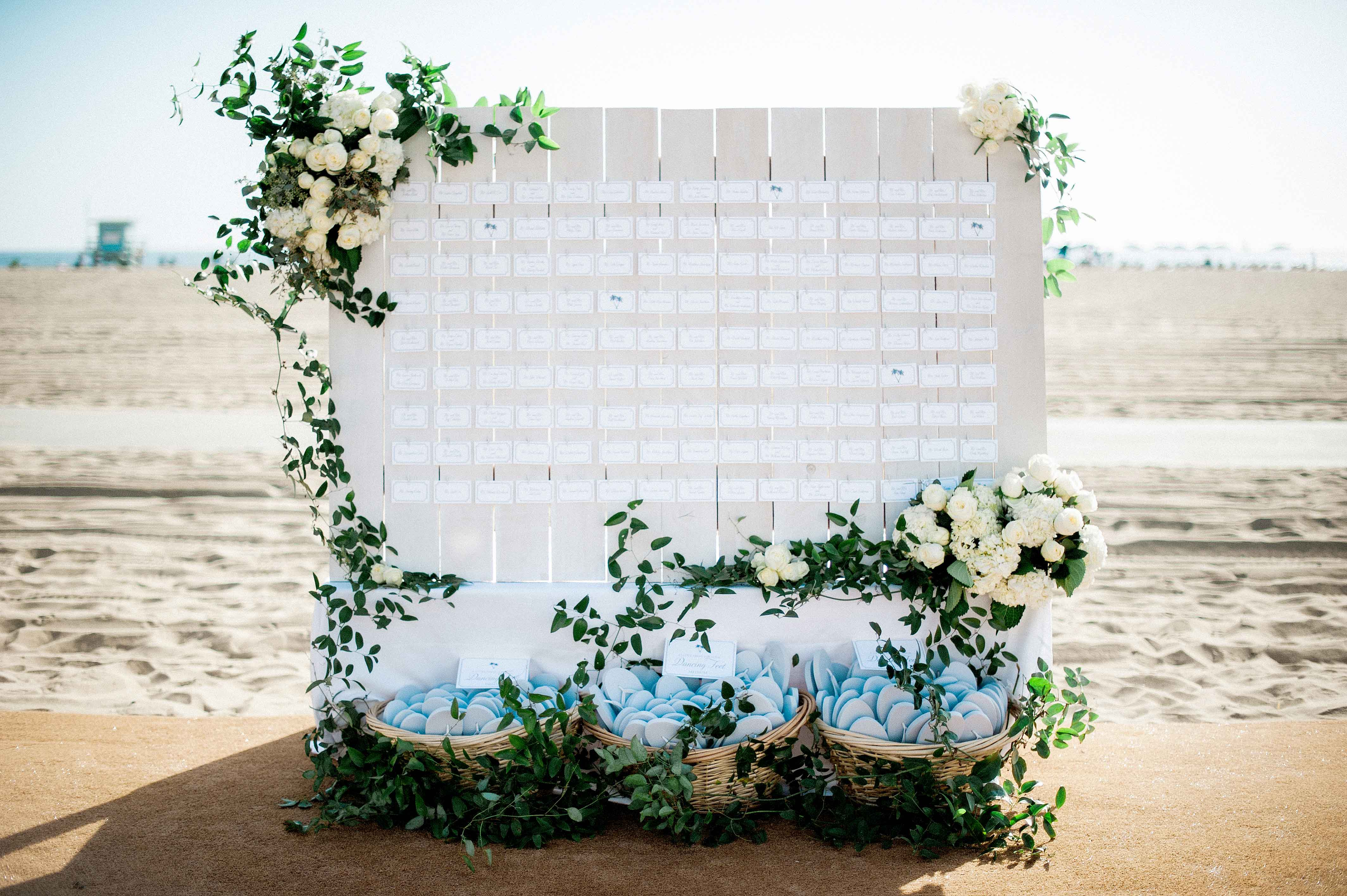 Beach wedding seating chart on boardwalk sand with flip flops