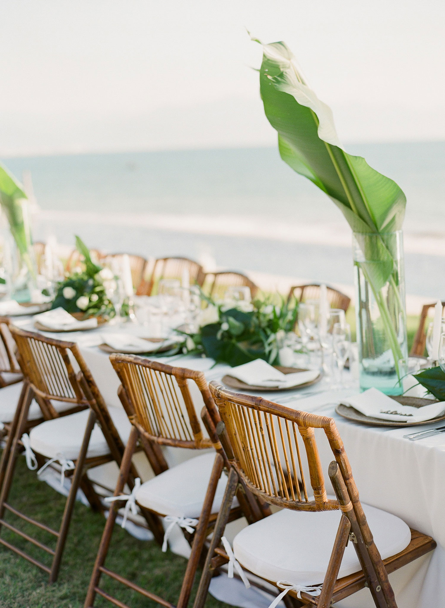 Destination wedding with ocean view wood rattan seats and tropical centerpieces