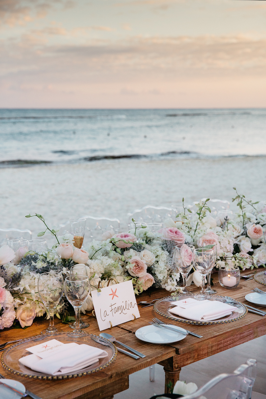 Destination wedding reception with ocean view at sunset on beach in Mexico