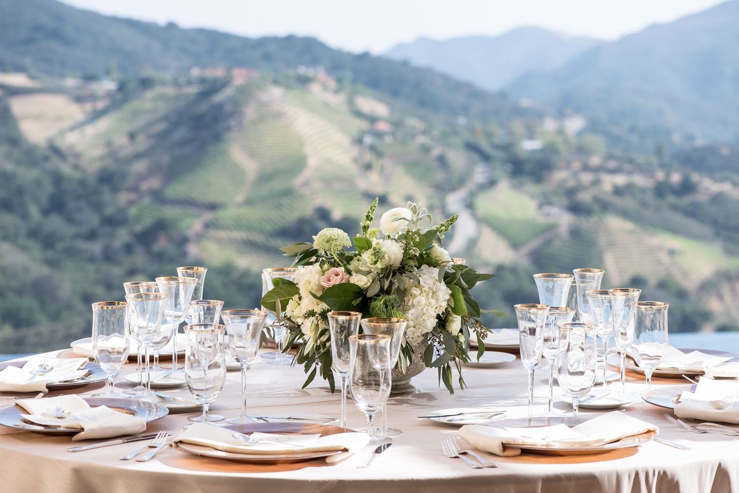 Outdoor wedding with view round table low flower centerpiece