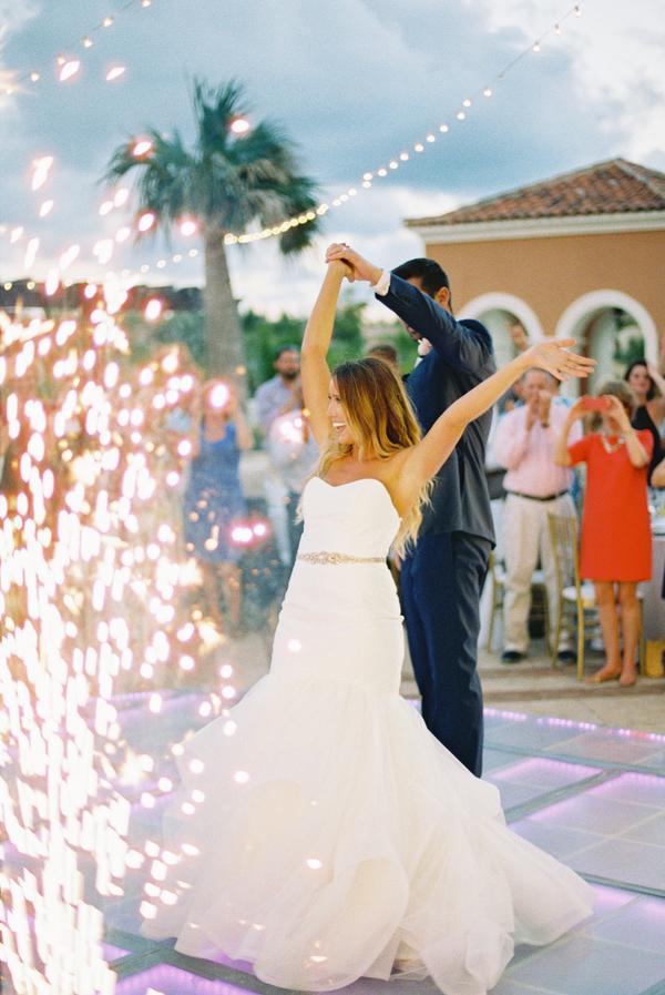Bride and groom dancing to first dance outdoor wedding reception firework lights