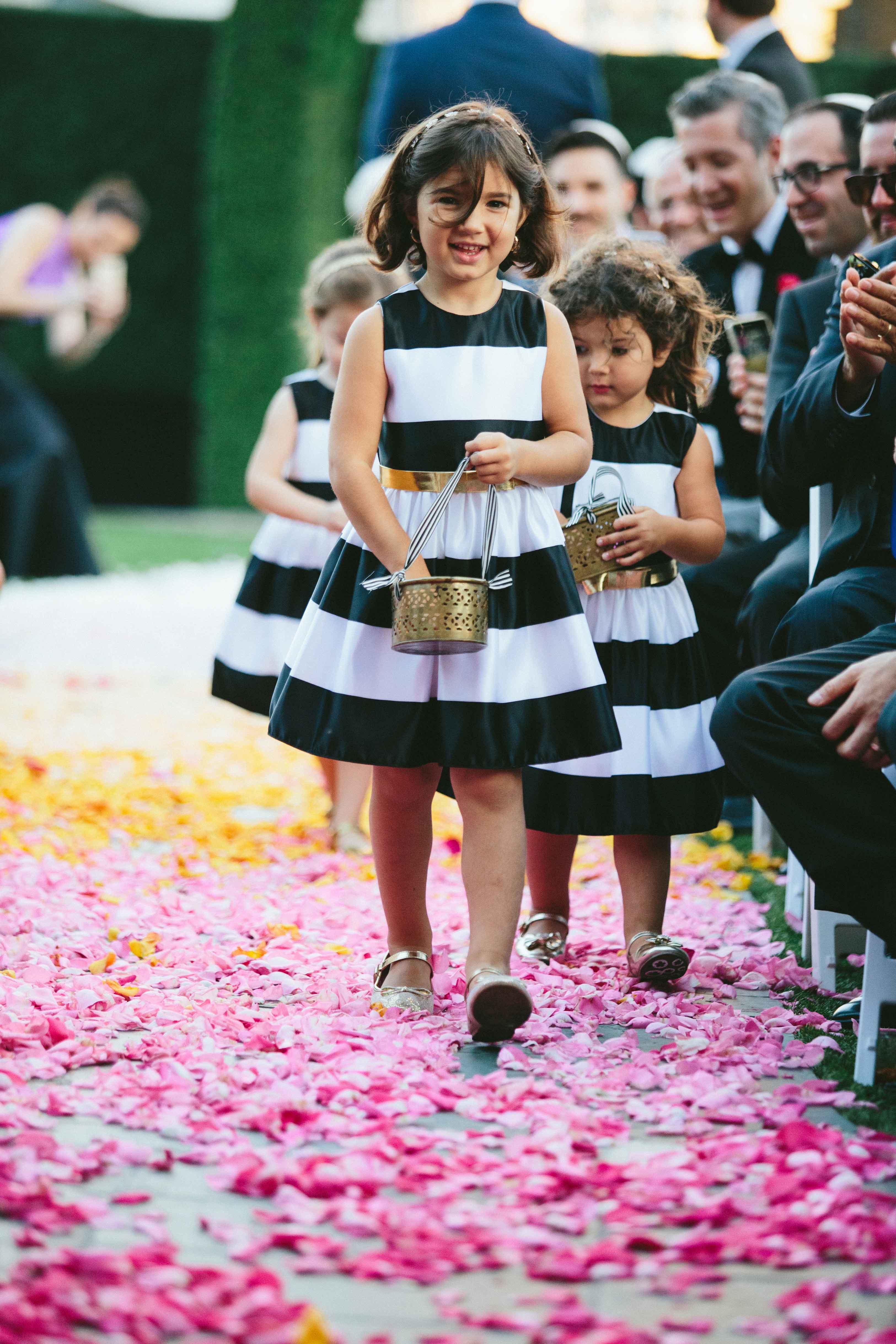 Black and white stripe flower girl dresses walking down petal aisle