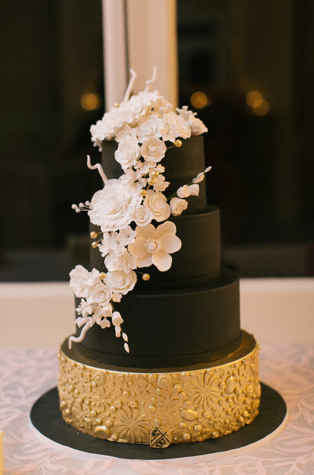 Black wedding cake with gold base and white sugar flowers on side