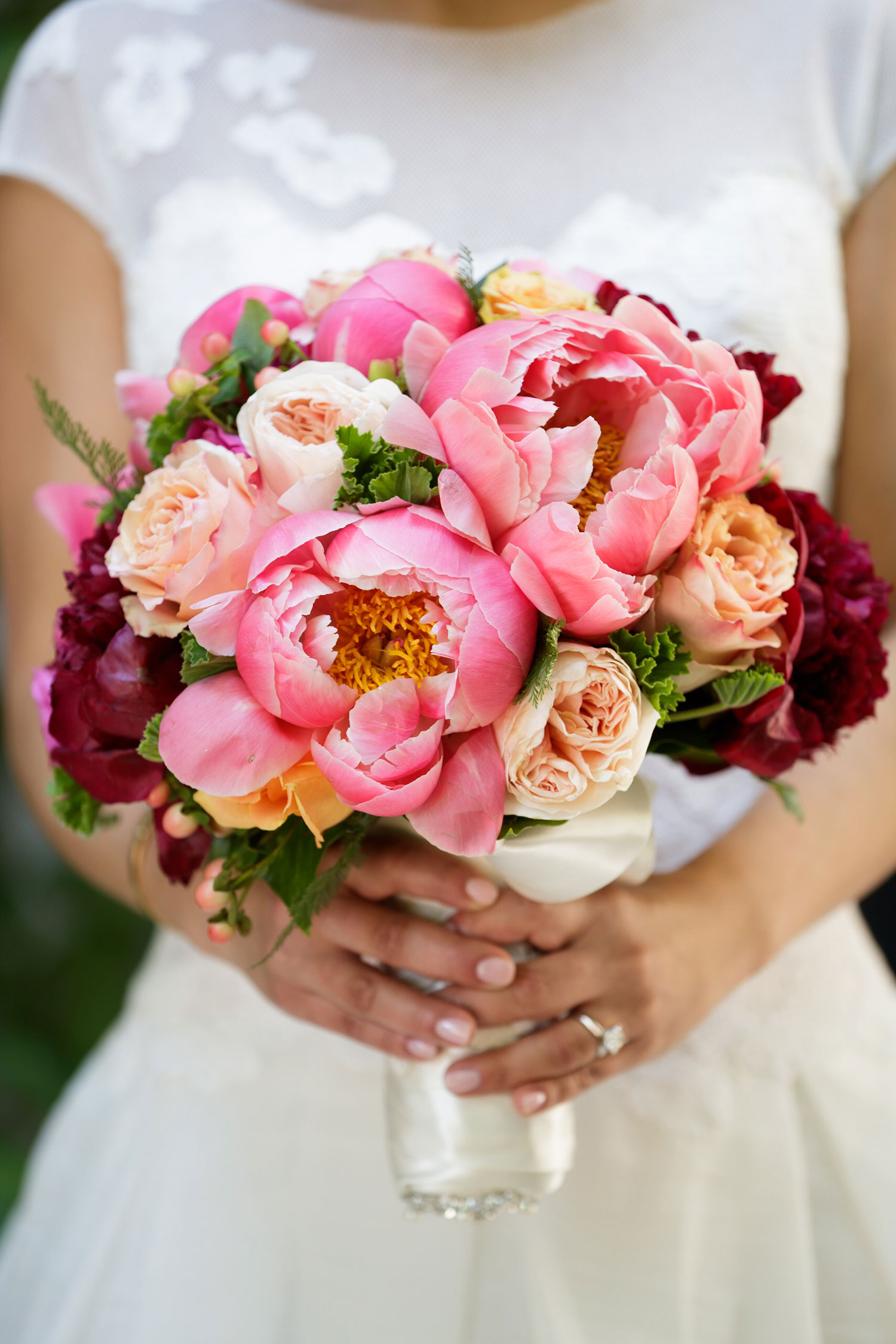 Bride holding pink peony wedding bouquet pink and red flowers