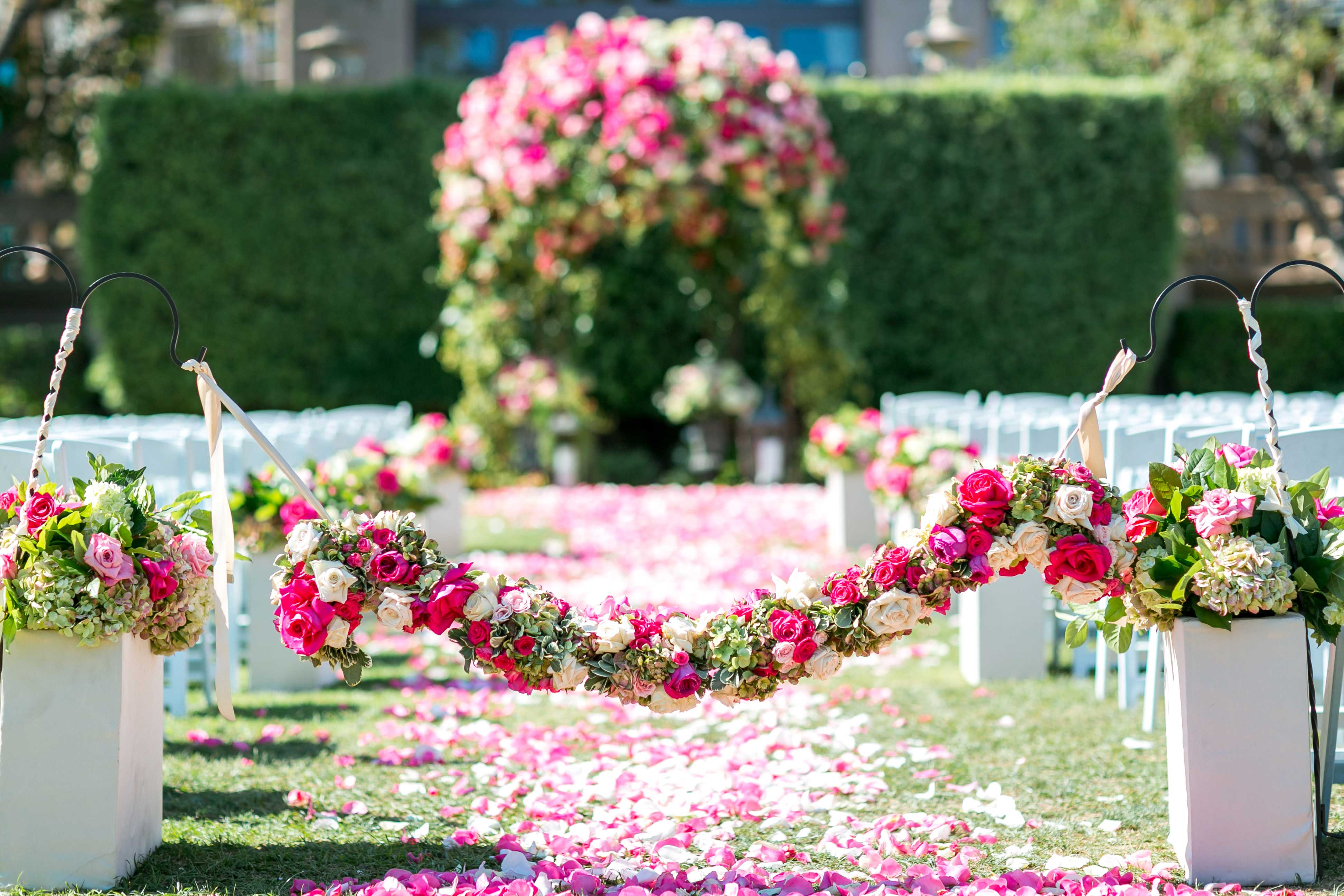 Outdoor wedding ceremony vow exchange with bright pink flowers