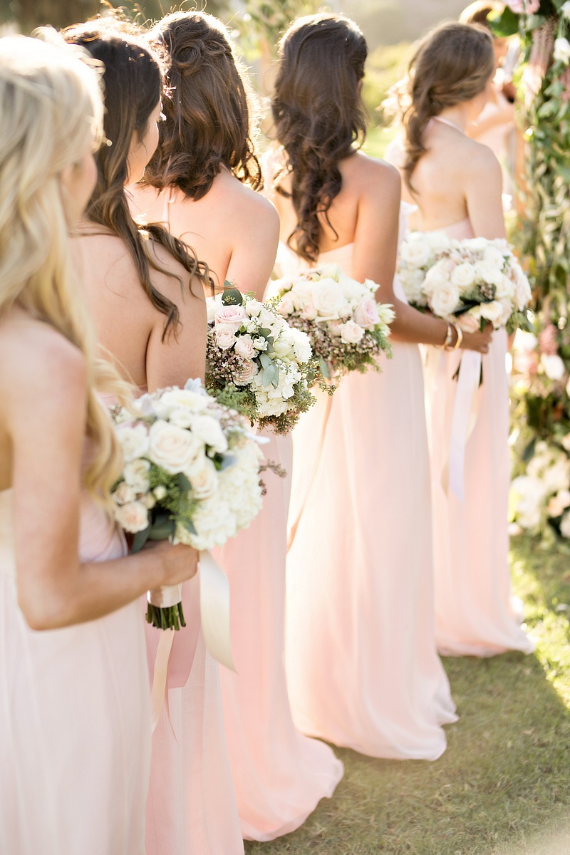 Bridesmaids at outdoor wedding ceremony in long light pink dresses