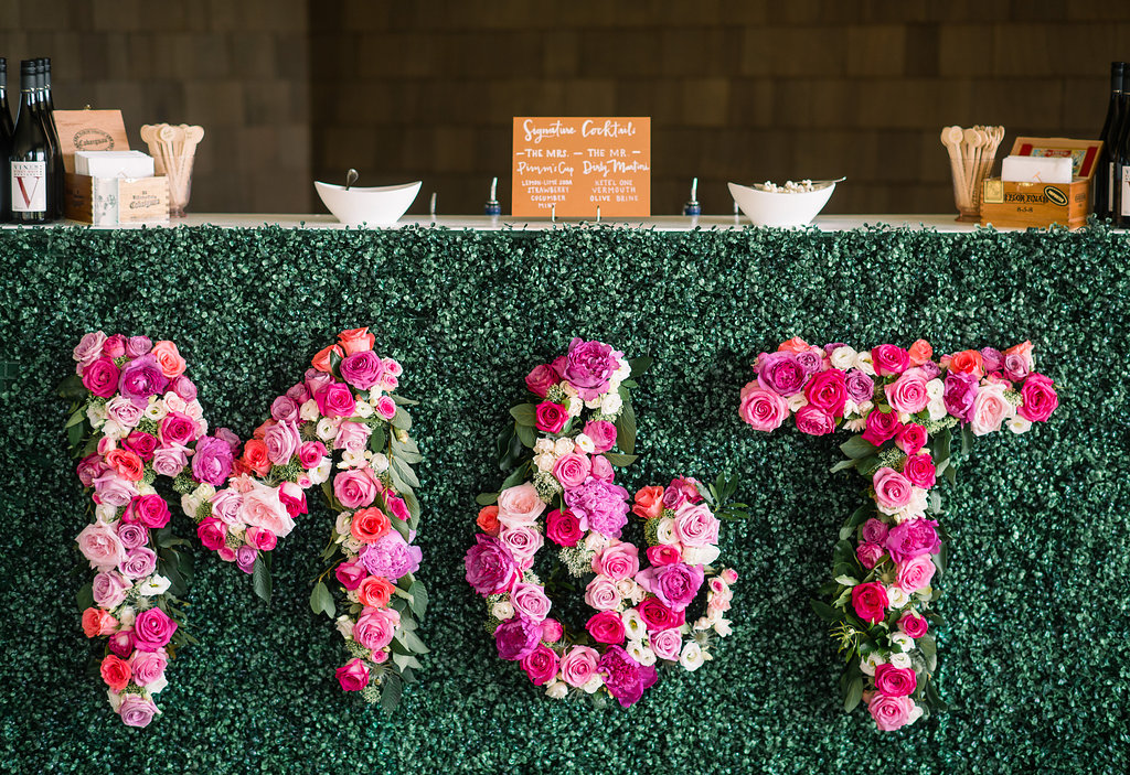 Wedding cocktail hour reception hedge wall pink initial flowers monogram