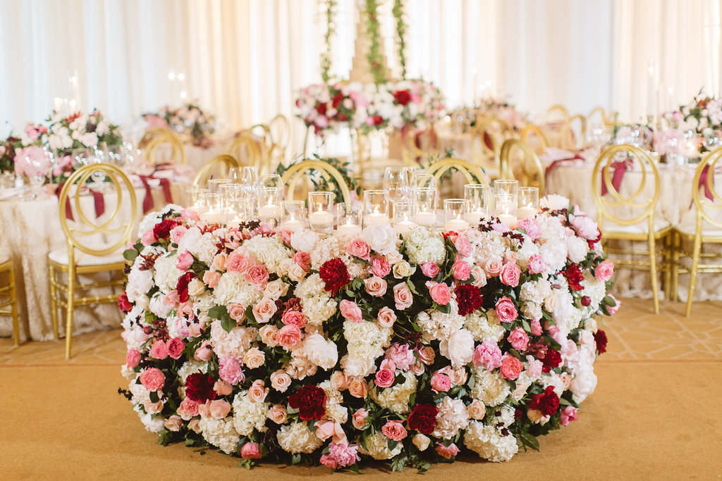 Sweetheart table ballroom wedding reception with pink and red flowers