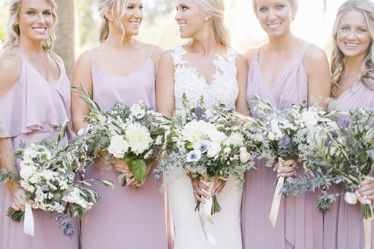 Bridesmaids in lavender purple gowns holding bouquets