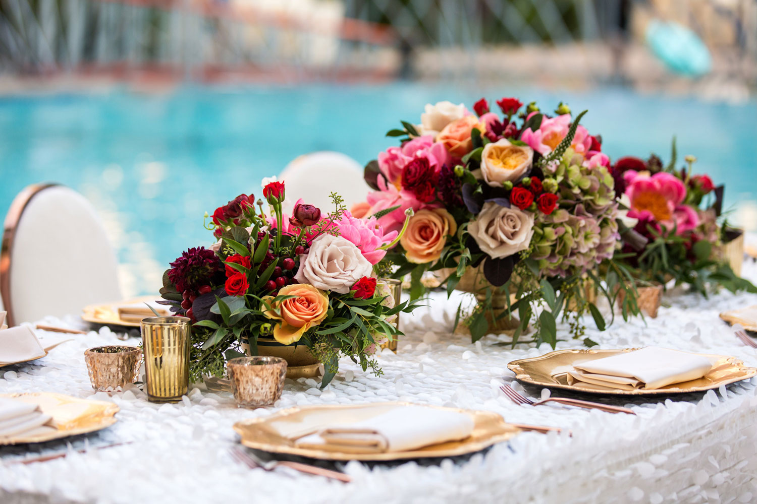 Colorful bold flowers on wedding reception table by pool