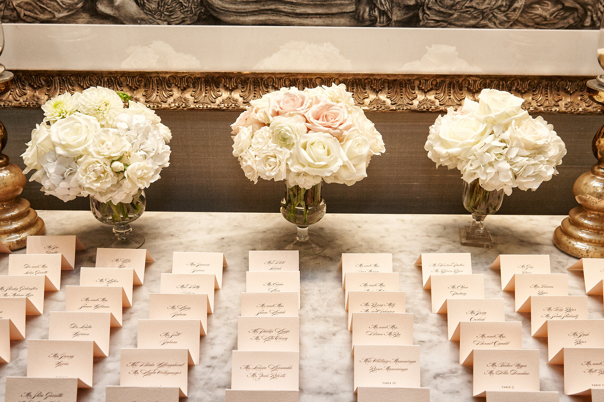 Escort cards on marble table at reception