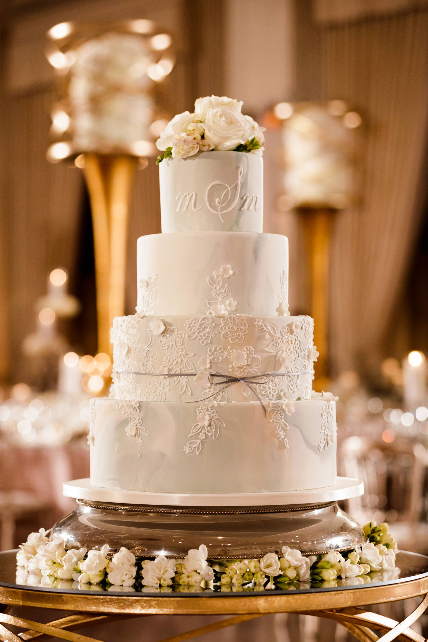 Wedding cake with monogram and bow inside weddings spring 2018 issue bob and dawn davis photography