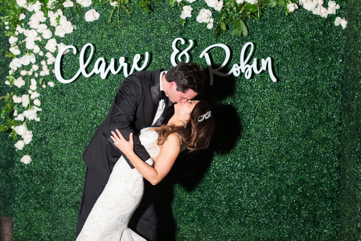 Bride and groom kissing in front of green hedge wall with names