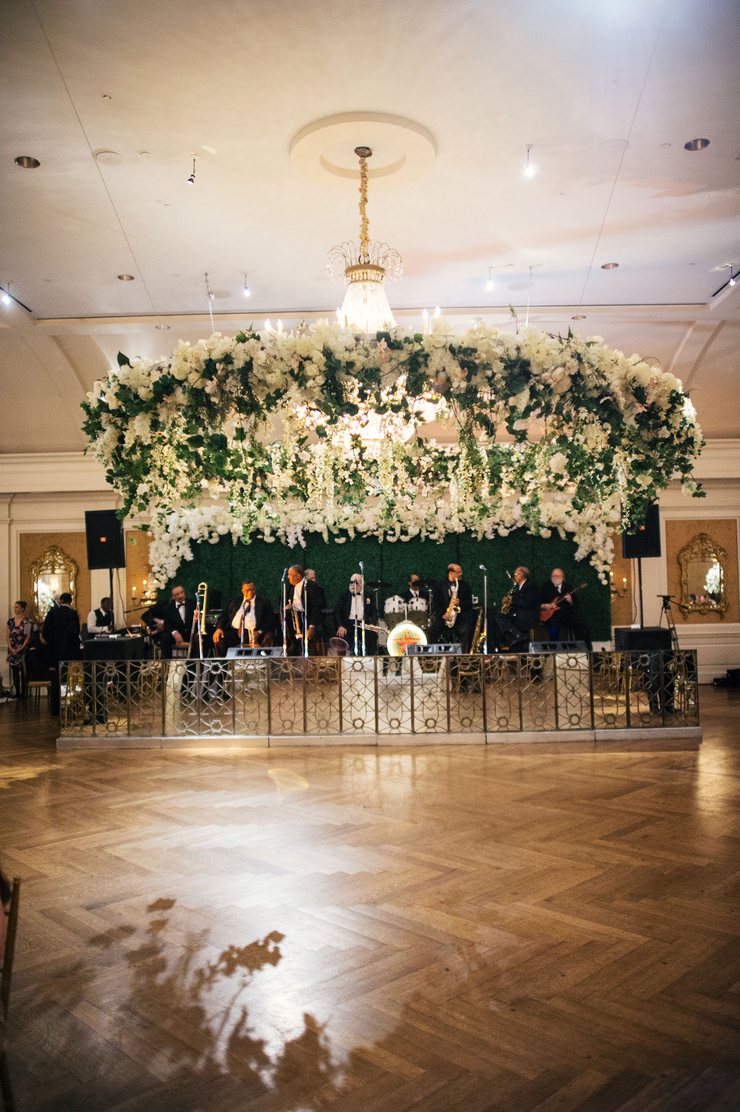 Flower and greenery wreath floral installation ceiling wedding reception over dance floor