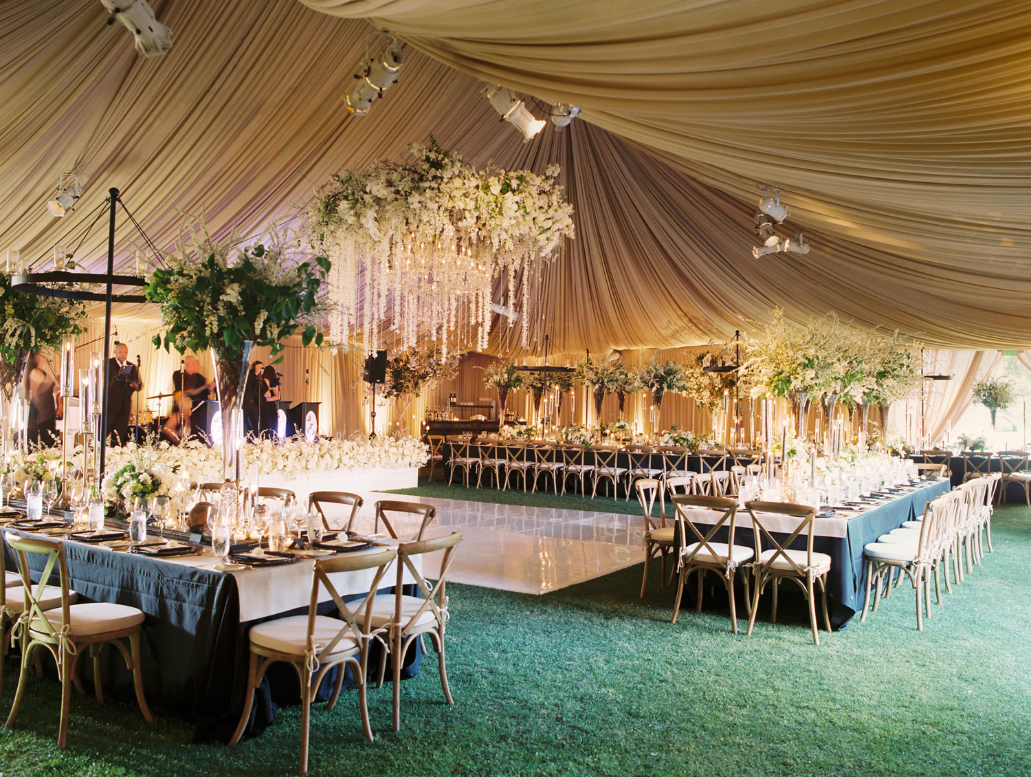 Large flower chandelier neutral color tented wedding reception over dance floor
