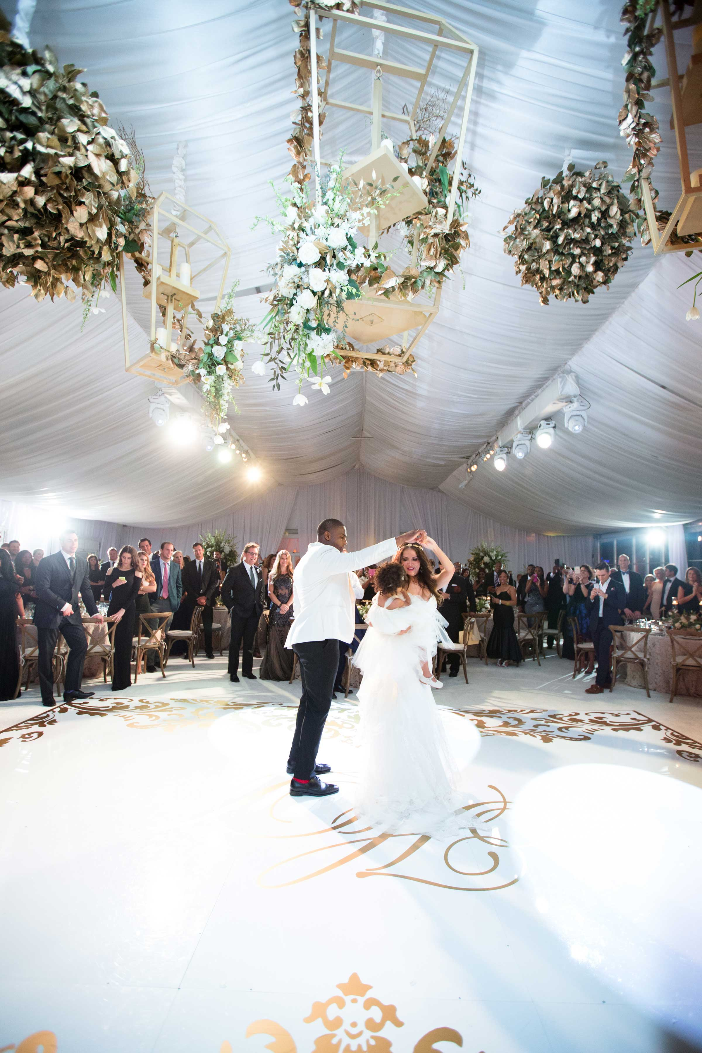 Demarco Murray and Heidi Mueller dancing with daughter on dance floor under large lanterns