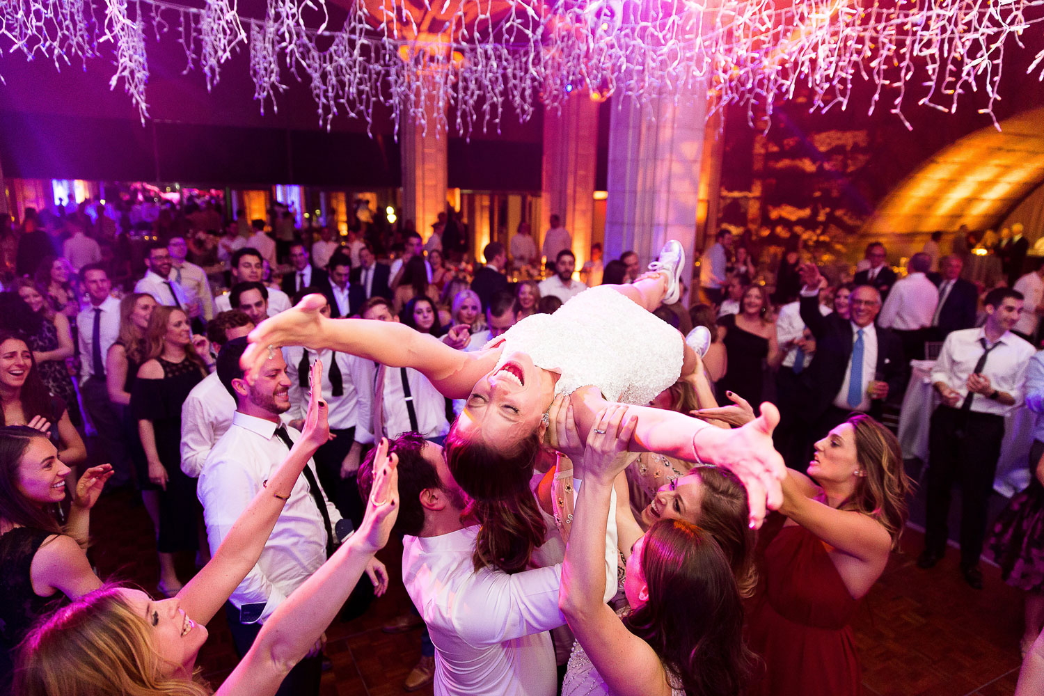 Bride crowd surfing at wedding reception icicle string lights over dance floor