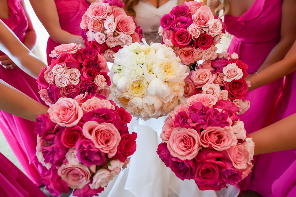 Bridesmaids holding bright and light pink colored bouquets