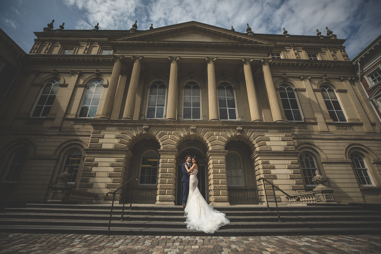 Bride in wedding dress with groom in front of Osgoode Hall in Toronto engagement shoot