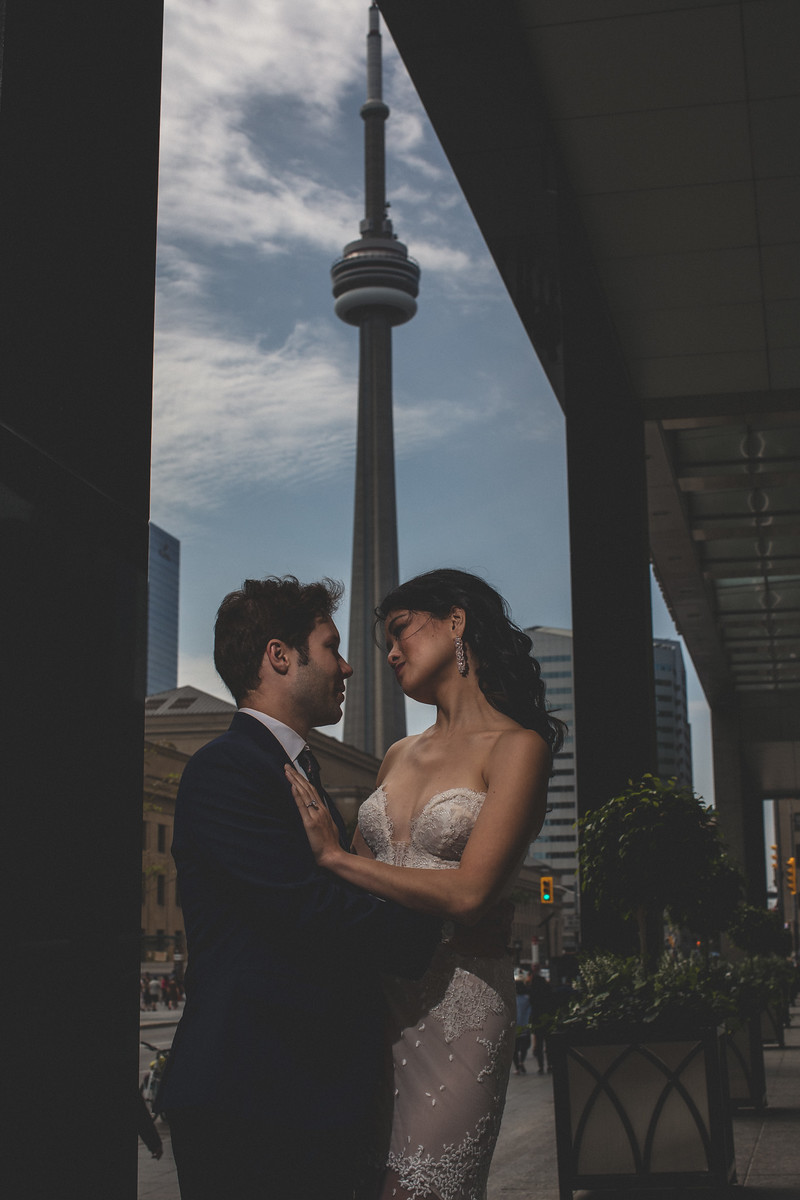 Bride in wedding dress engagement shoot with groom in front of CN Tower Toronto engagement shoot ideas