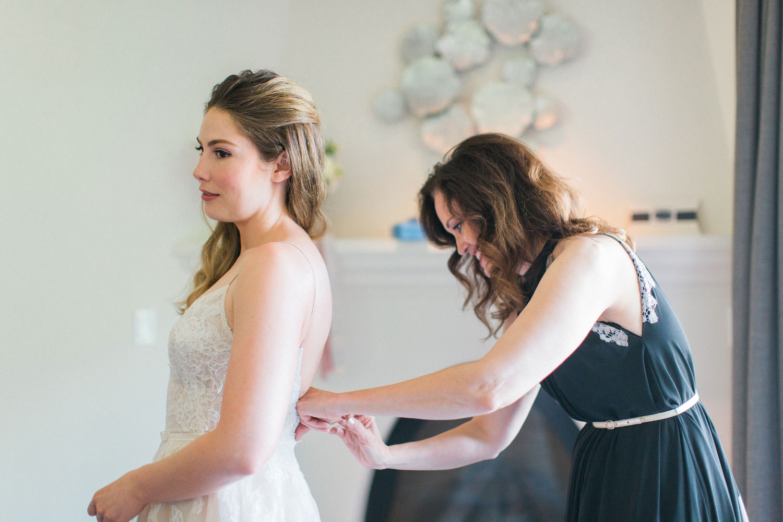 Maradee Wahl of Dear Maradee sewing ribbon sash on bride dress on day of wedding bridal stylist duties