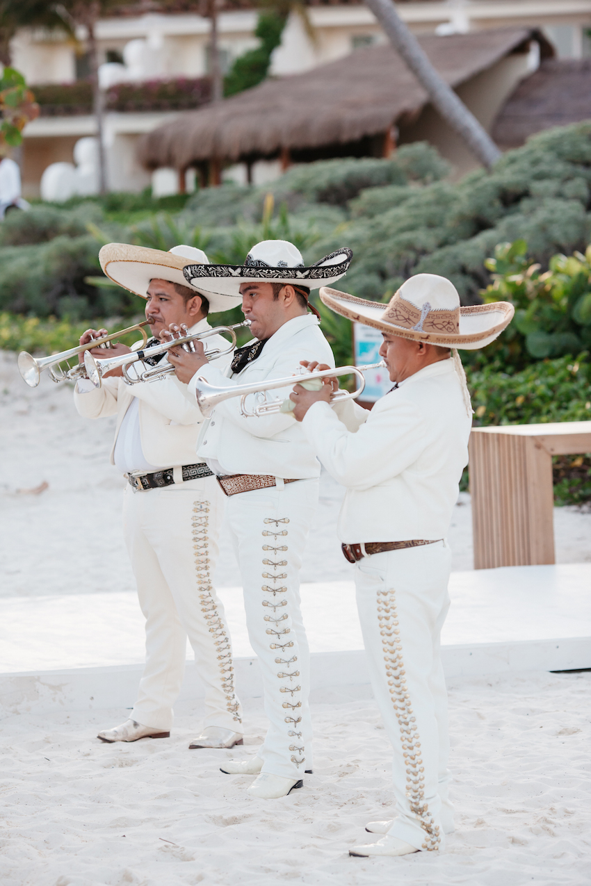 Mariachi performers dressed in white performing at wedding mariachis in sand