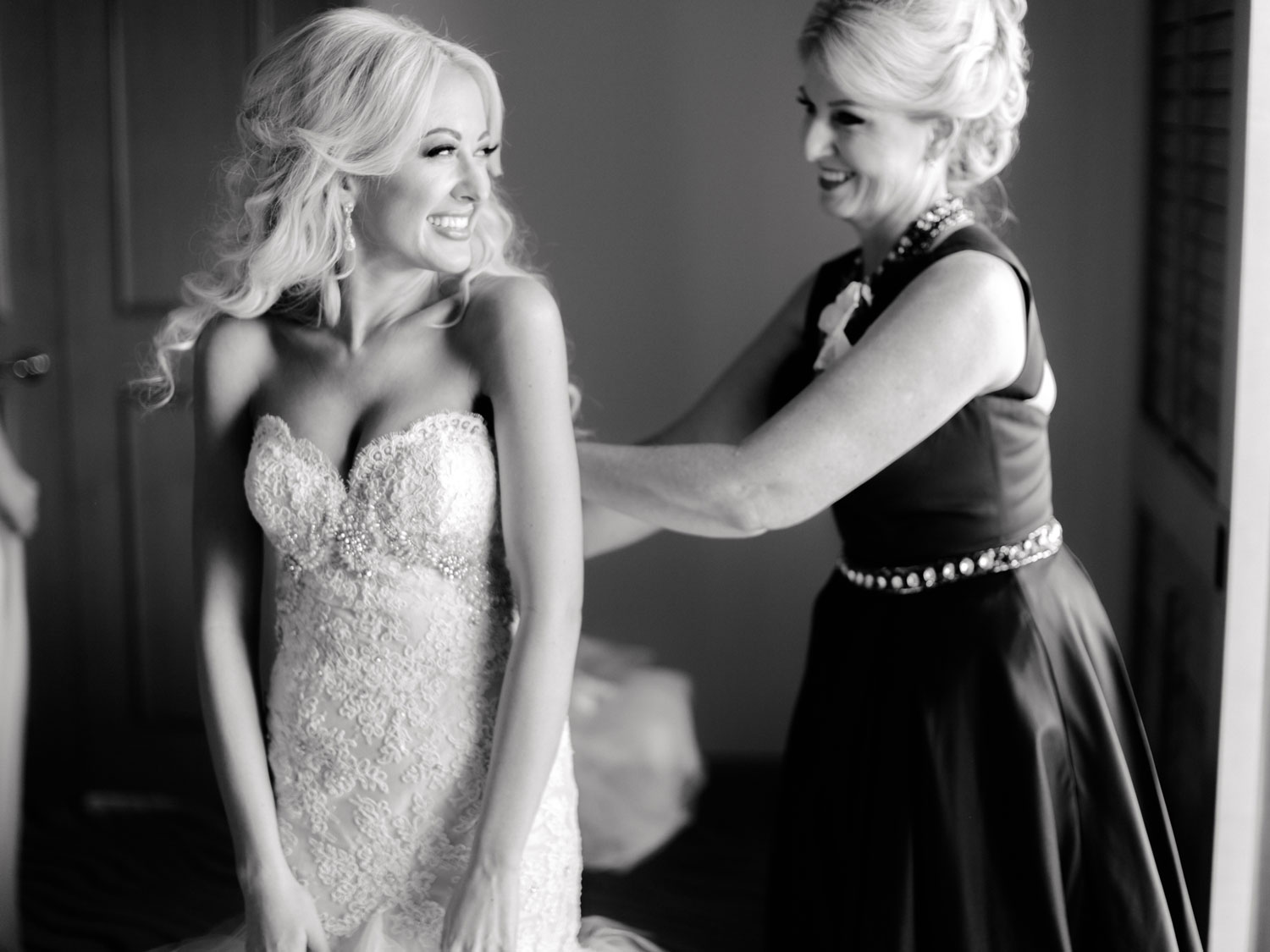 Black and white photo of bride smiling as her mom helps her into her gown wedding