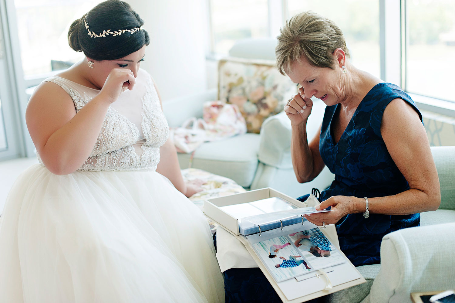 Mother of bride and bride crying happy tears while looking through photo album wedding day