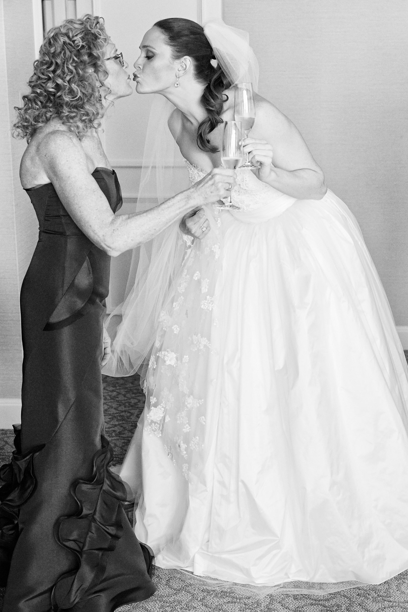 Black and white photo of bride and mother with champagne giving kiss before wedding