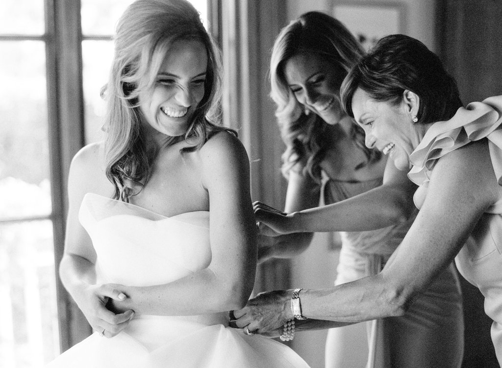 Sister and mother of bride helping bride put on wedding dress black and white photo