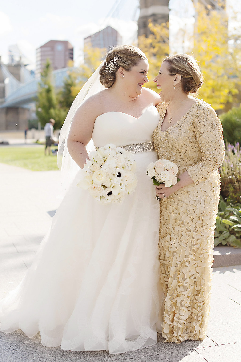 Bride and mother of bride in gold gown smiling with each other